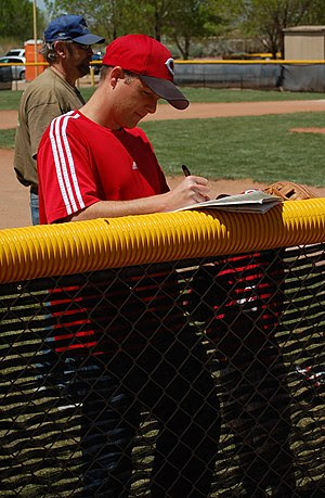 English: A tee ball coach setting the lineup a...