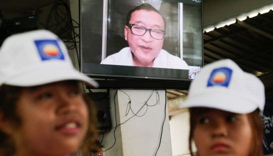 CNRP youths listen to Sam Rainsy speak via video link yesterday morning at party HQ.
