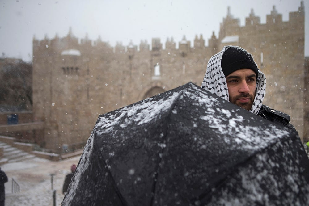A Palestinian man stands in the snow at Damascus gate outside Jerusalem's old city. (Uriel Sinai/Getty Images)