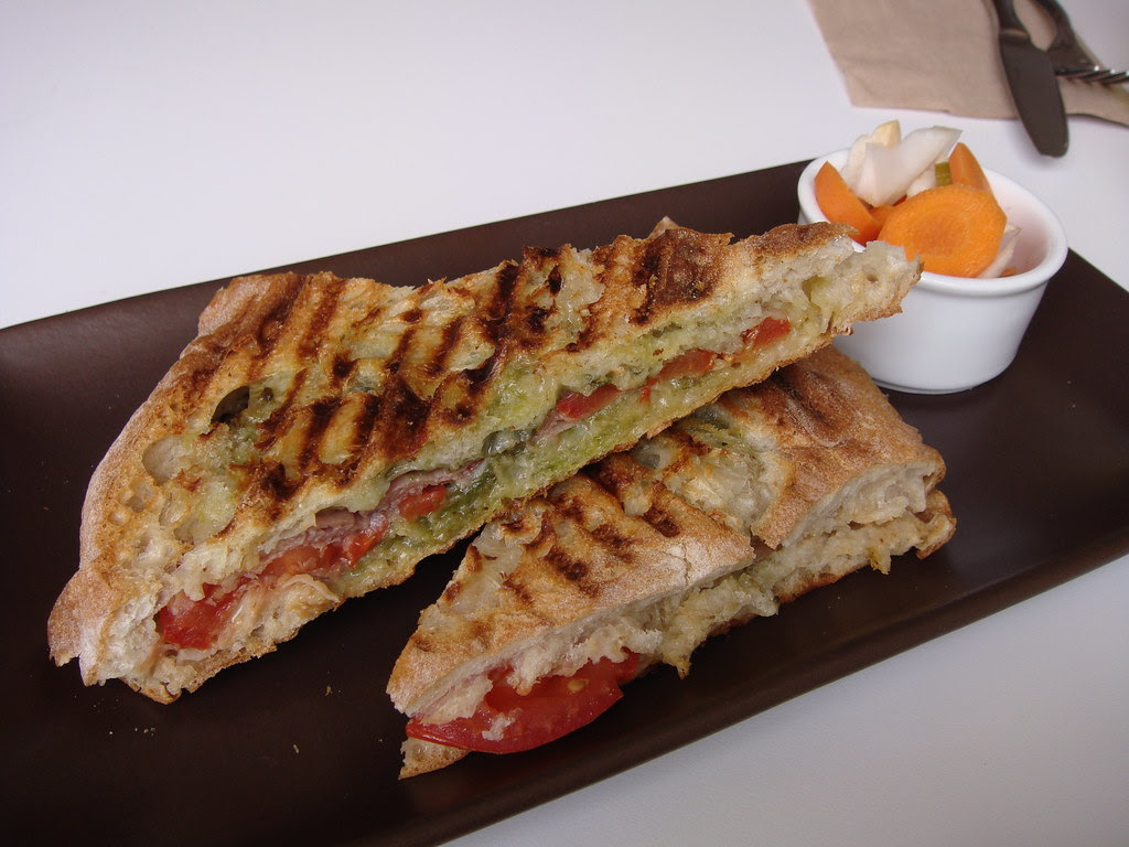 Prosciutto and mozzarella panini with tomato and pesto spread