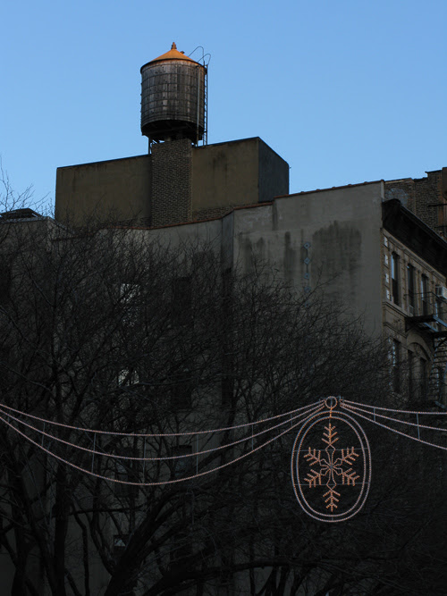 Christmas decoration lights and a water tower at sunset, Manhattan, NYC