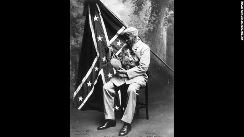 A decade after the end of the Civil War, a veteran of the Confederate States of America examines a Union water bottle in front of a Confederate flag in 1875. Here's a look at the evolution of that flag: