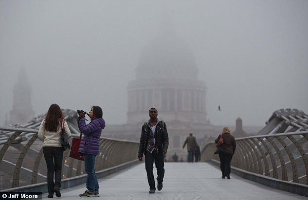 St Paul's Cathedral is just a shadow in the background as people make their way across Millennium Bridge