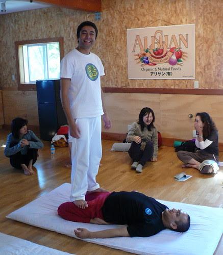 Yoga teacher Nirmal, standing on his assistant Naresh, demonstrating yogic massage
