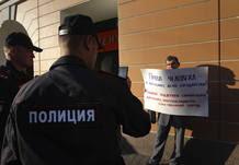 """Unos policías fotografían con un móvil el cartel que sostiene un manifestante, en el que se lee """"Los Derechos Humanos no son asuntos internos de un estado. No al apoyo al dictador de Siria, que arrasa la nación"""""""