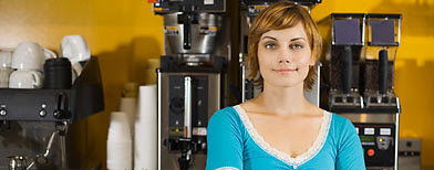 Woman standing beside espresso machine  (Photo by Jupiterimages)