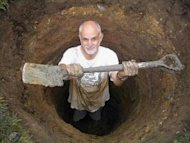 Man in a hole, showing a shovel