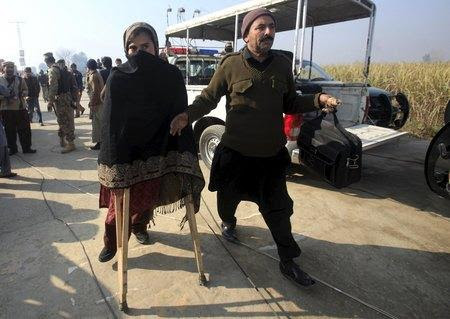 A teacher walks with a pair of crutches following her rescue after a group of militants stormed the Bacha Khan University in Charsadda