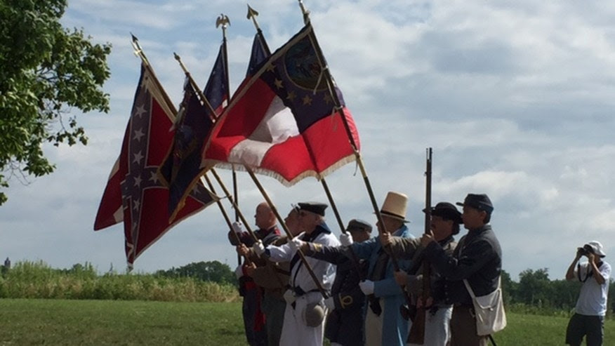 A group of reenactors march in formation from the North Carolina Memorial along West Confederate Ave to the Virginia Memorial at Gettysburg.