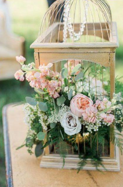einen Vogelkäfig mit Kristallen, üppigem grün und rosa Blüten für einen Garten Hochzeit