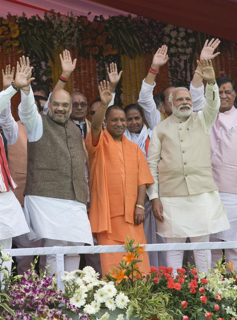 Indian Prime Minister Narendra Modi, second right, Yogi Adityanath, center in saffron robes, and Bharatiya Janata Party president Amit Shah, left and others wave to the audience after Adityanath was sworn in as Uttar Pradesh state chief minister in Lucknow, India, Sunday, March 19, 2017.