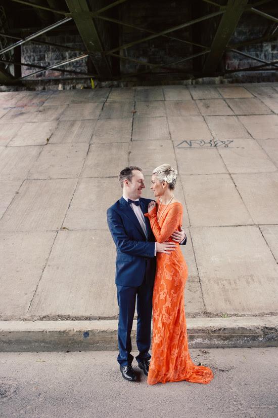 die Braut rocking einem kräftigen orange-Spitze-Hochzeits-Kleid mit langen ärmeln und eine Perlenkette