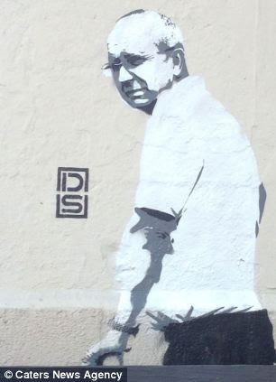 Centre of attention: A stenciled representation of the worker from Islington Council is now featured on the same wall he was sent to clean up