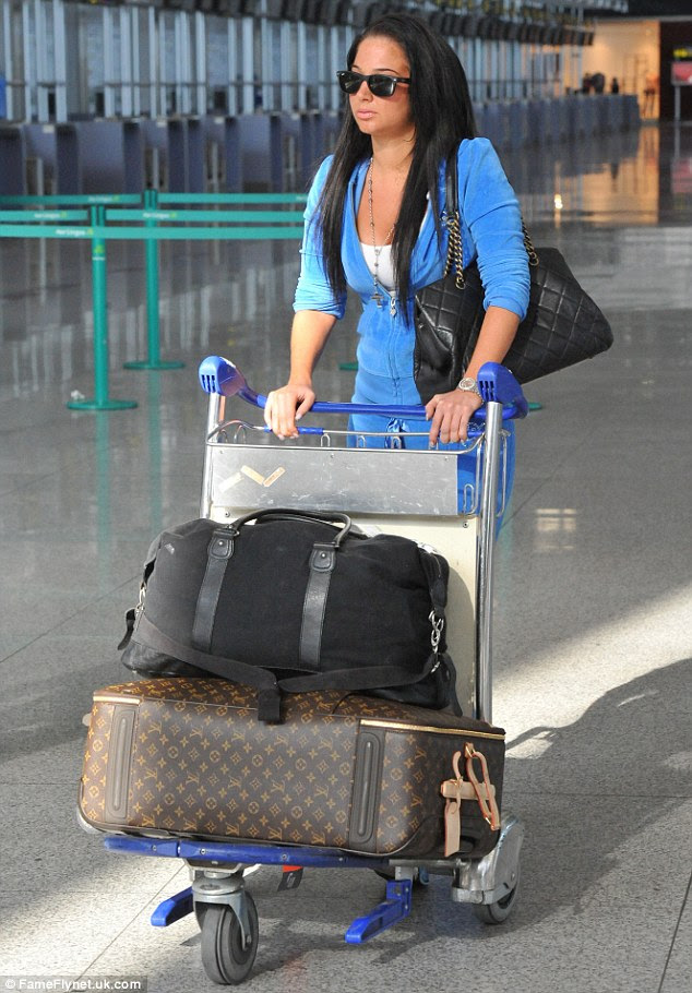 Homeward bound: Tulisa covered her eyes with dark shades as she prepared to make the journey to her man's side