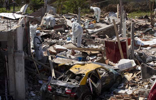 Equipes trabalham no local da explosão nesta segunda-feira (26) próximo a Buenos Aires (Foto: AP)