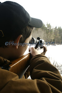 hunter aiming a rifle through the sight