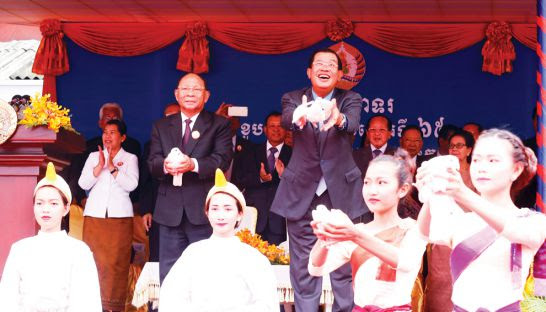 Prime Minister Hun Sen (right) and National Assembly President Heng Samrin release doves at a celebration of the ruling Cambodian People's Party's 65th anniversary yesterday.