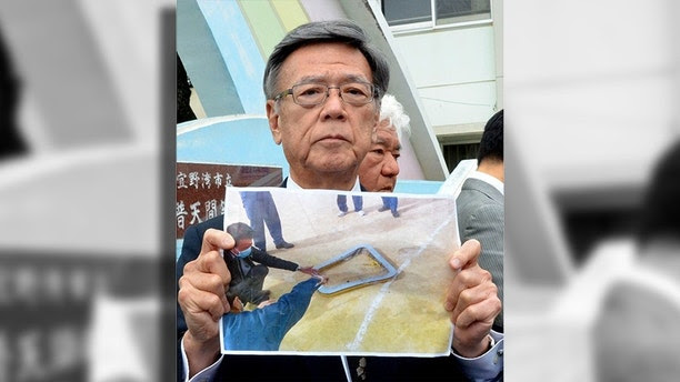 Okinawa Gov. Takeshi Onaga, holds a picture of a metal window frame fallen from U.S. military aircraft CH-53 outside an elementary school in Ginowan, Okinawa Wednesday, Dec. 13, 2017. Japanese officials say a boy was injured in Okinawa when the metal window frame fell from a U.S. military helicopter, escalating anti-American sentiments on the southern island. (Kazuki Sawada/Kyodo News via AP)