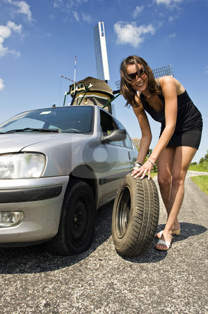 Beautiful Woman Fixing Flat Tire Stock Photo