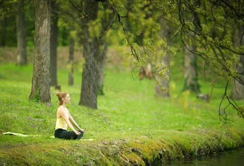 Mulher meditando na margem de um rio