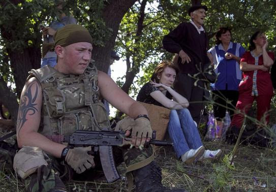 Ukrainian army soldier from battalion 'Aydar' guards local residents as they leave the village of Metalist near the eastern Ukrainian city of Luhansk July 11, 2014. REUTERS-Viktor Gurniak