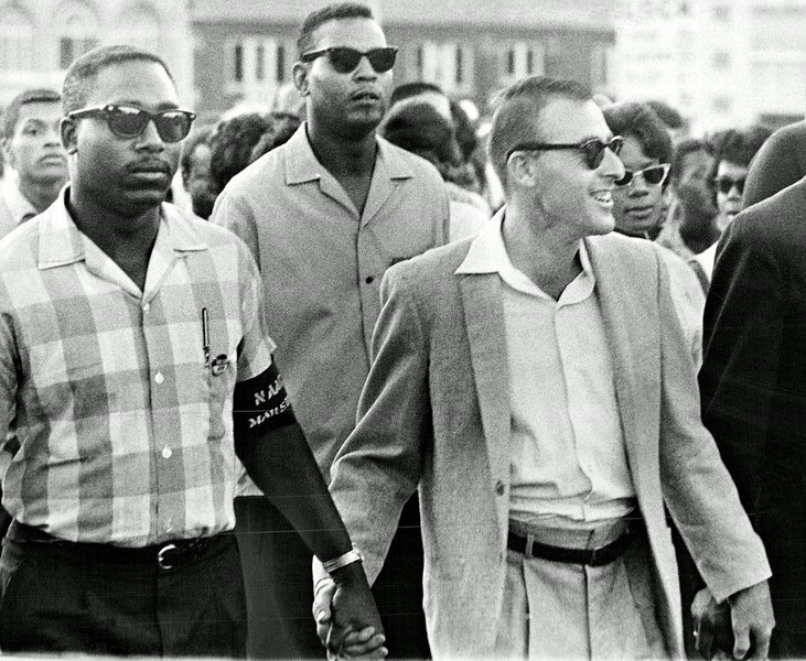 Description of  JUN 25 1963 - White and black marchers join hands as they approach the Denver City and County Building Tuesday night during a demonstration to protest alleged discriminatory practices. They came to attend a race-relations conference in Council Chambers. (Duane Howell/The Denver Post)