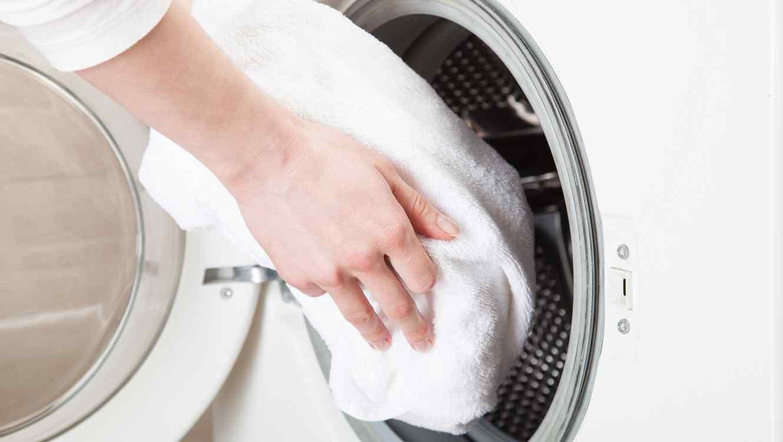 Mujer colocando toallas blancas dentro de una lavadora
