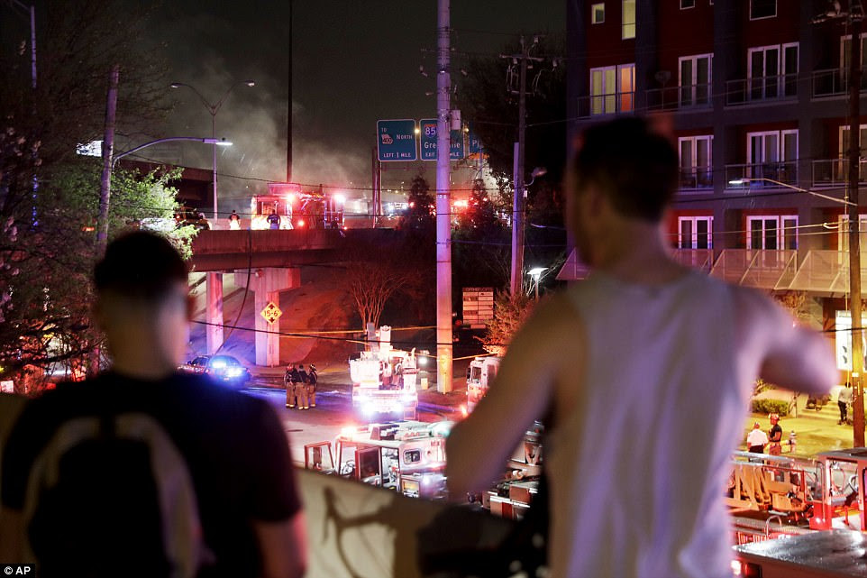 Bystanders watched as smoke billowed from a section of the overpass that collapsed from the massive fire on I-85