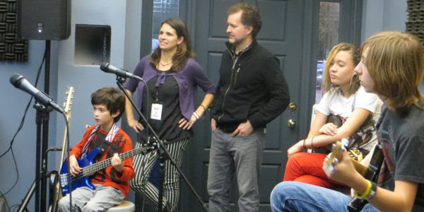 Tory and Vanessa Ridder stand behind their son Wolfe, 9, while watching students in the School of Rock's performance program practice at their weekly band rehearsal. Photo by Danielle Brody