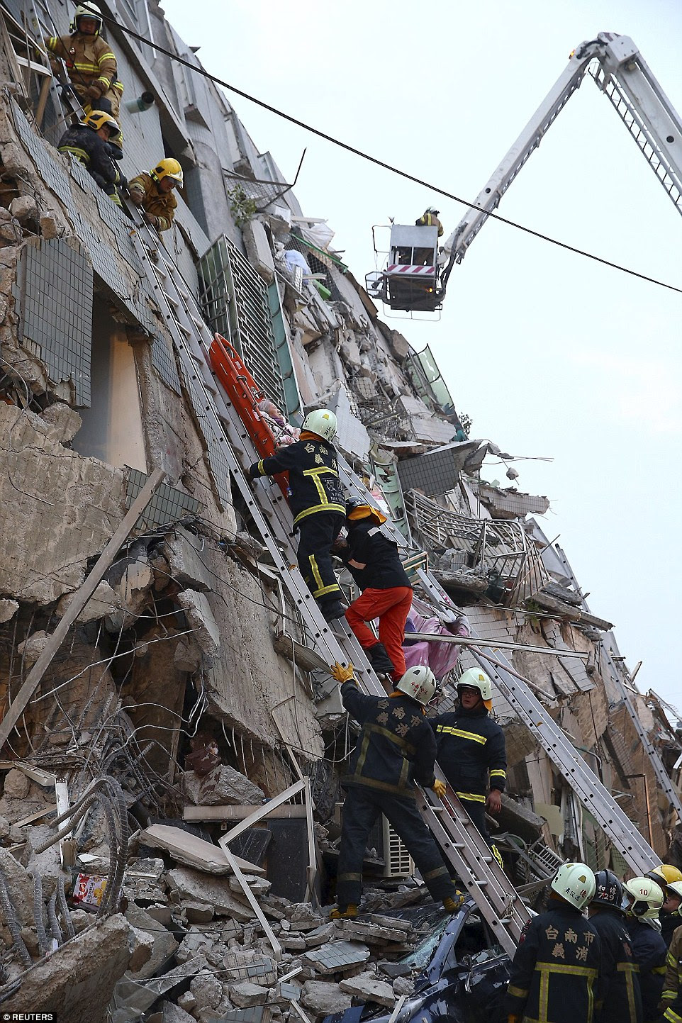 Rescuers climb up the mangled ruins of the apartment block to reach people trapped on the higher floors