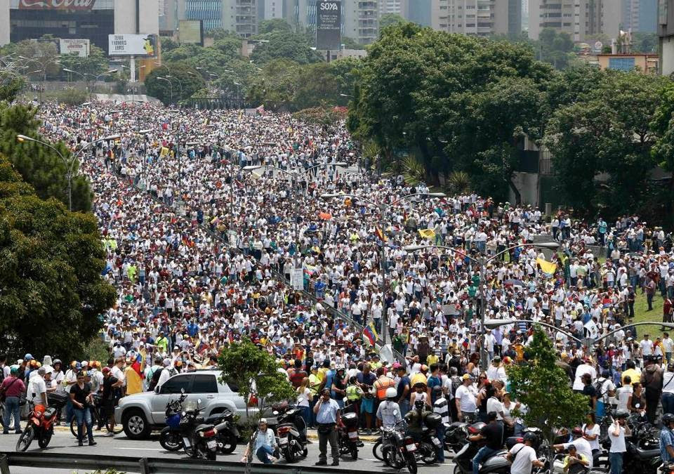 Anti-government protesters march along a highway in Caracas, Venezuela, Wednesday, April 19, 2017. Tens of thousands of opponents of President Nicolas Maduro flooded the streets of Caracas in what's been dubbed the