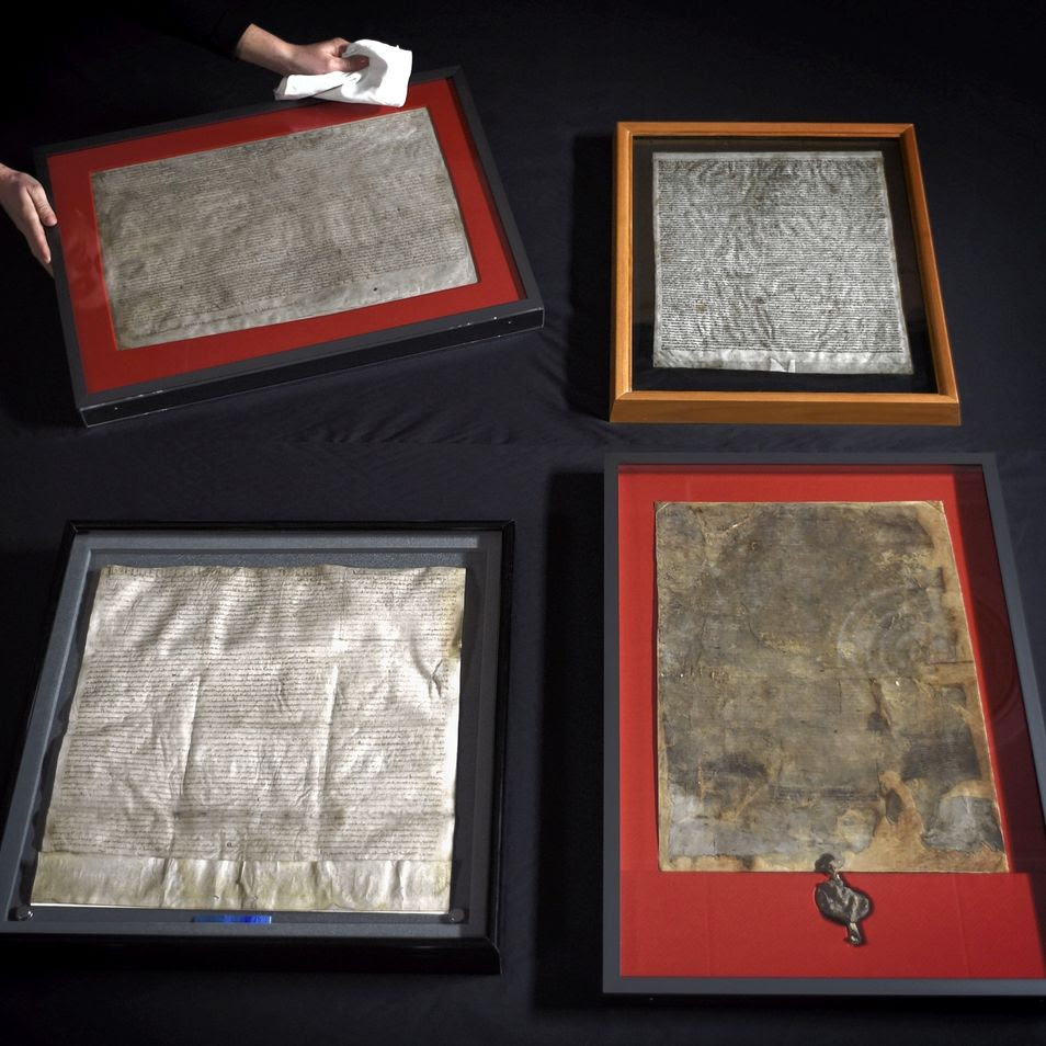 United for the first time, the four surviving original Magna Carta manuscripts are prepared for display at the British Library, London, Feb. 1, 2015.