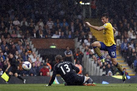 Arsenal's Olivier Giroud (R) scores past Fulham's goalkeeper David Stockdale during their English Premier League soccer match at Craven Cottage in London August 24, 2013. REUTERS-Stefan Wermuth