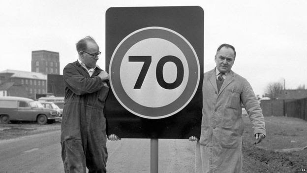 Workmen carrying 70 miles per hour sign in 1965