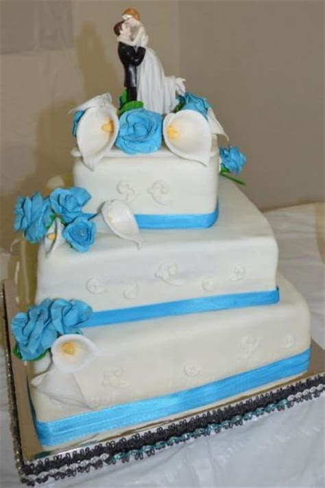 3 tier square white offset wedding cake with blue band and