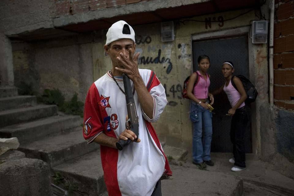 """Un traficante de drogas que se identificó a sí mismo como """"El Menor"""", patrulla el barrio Las Mayas en Caracas en una foto de archivo."""
