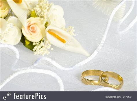 Picture Of Wedding Rings And Flowers Over Veil