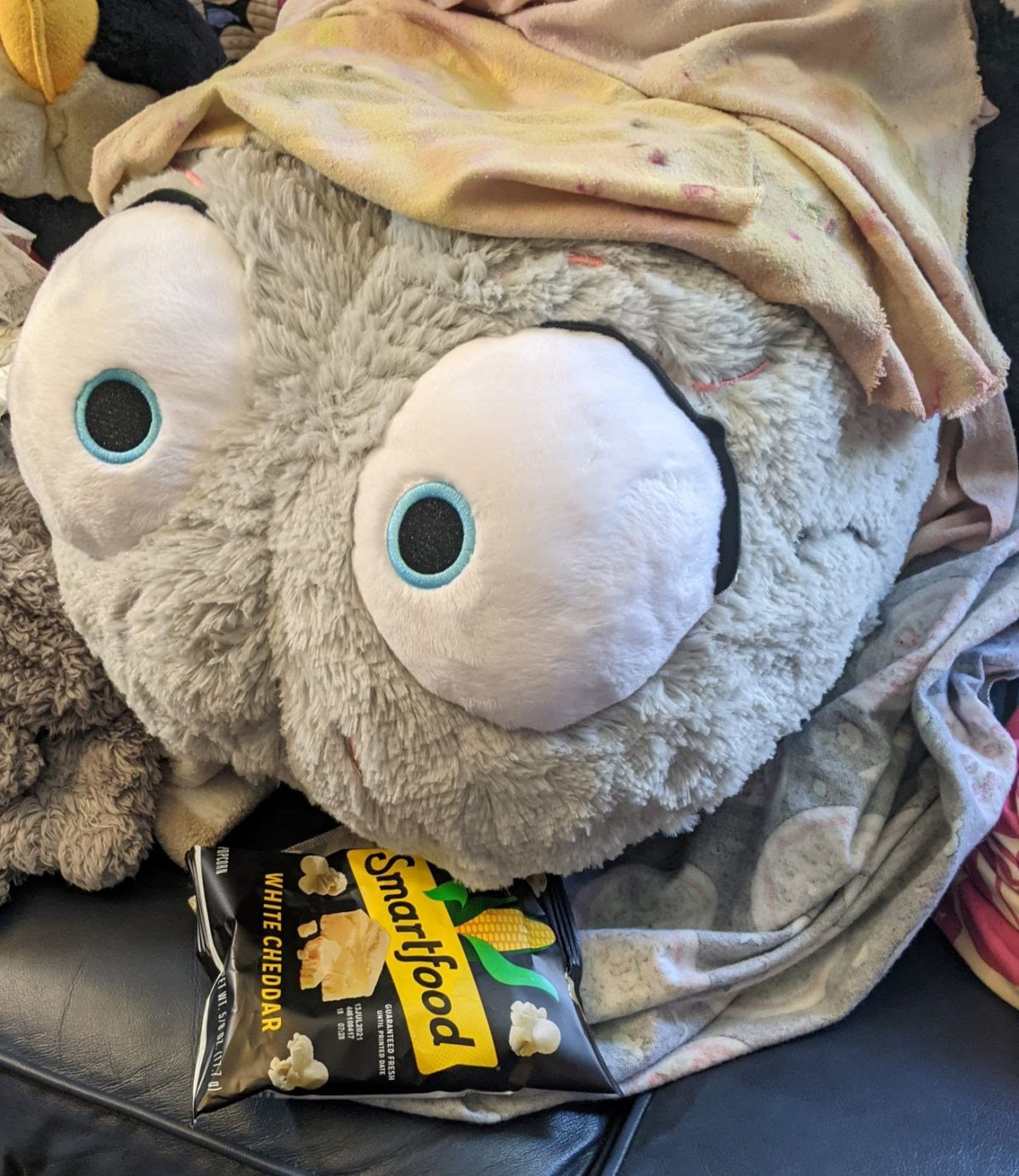 A gray plush brain with big eyes sits on a couch and appears to eat a bag of chips