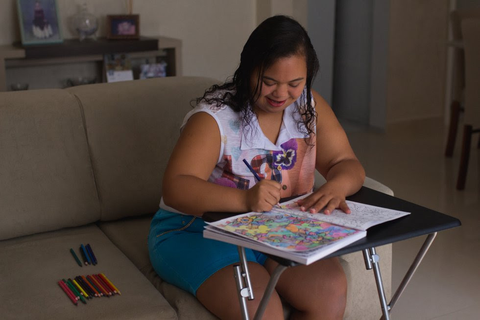 Priscila preenche seus livros de colorir.
