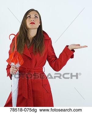 Stock Photo - woman in red trench  coat with umbrella  and expecting  rain. fotosearch  - search stock  photos, pictures,  wall murals, images,  and photo clipart