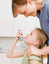 Madre mirando a su hija que usa un inhalador