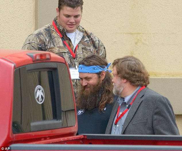 Under fire: Willie Robertson (center) leaves church today with his father (not pictured), who has been suspended from their reality television series for comments he made about homosexuality last week