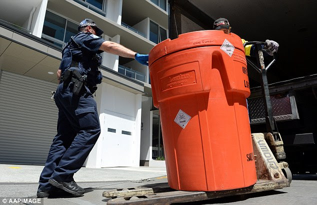 Queensland Police removed a toxic-labelled container on Monday following the discovery of a woman's body parts found boiling in chemicals in a Brisbane apartment on Saturday night