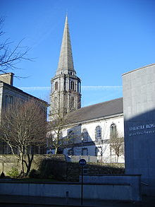 A Large Church spire can be seen above and behind a theatre and a deciduous tree with leaves shed.