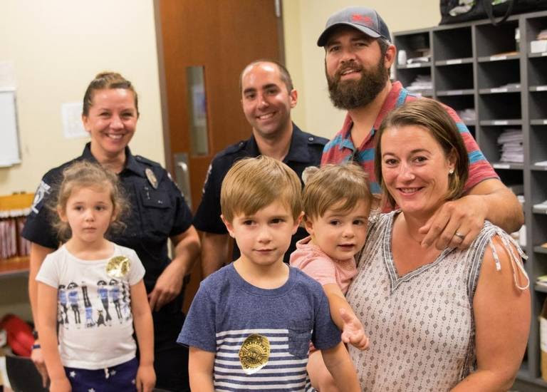 CMPD officer Nikolina Bajic (left rear) and Lawrence Guiler stand with John and Sarabeth Ogburn and their kids (from left) Birdie, four, Huck, five, and Revel, two, on Tuesday. Guiler and Bajic saved John's life a few weeks ago when they performed CPR on him for nearly 45 minutes after he had gone into caridac arrest inside a Panera Bread.