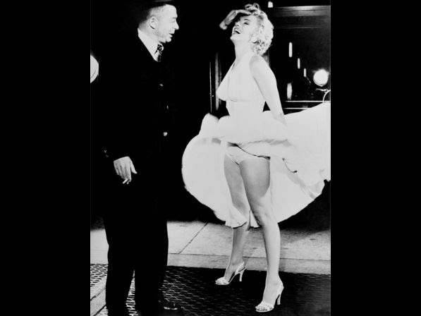 """Monroe stands over an air vent, which causes her dress to fly up as director Billy Wilder fixes her hair during filming of the movie """"The Seven Year Itch"""", which was released on June 3, 1955."""