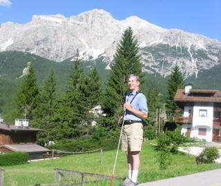 Mike exploring around, stopping long enough to pose for a picture in front of a mountain range in Cortina