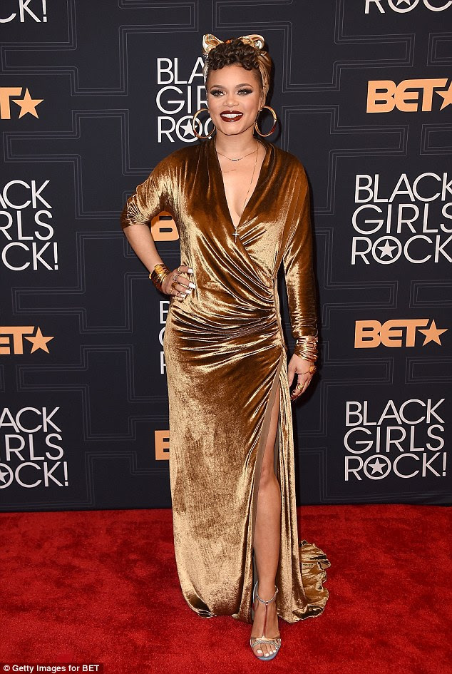 Golden girl: Andra Day fleshed some flesh in a slinky bronze dress that was teamed with matching accessories and a sexy pair of heels