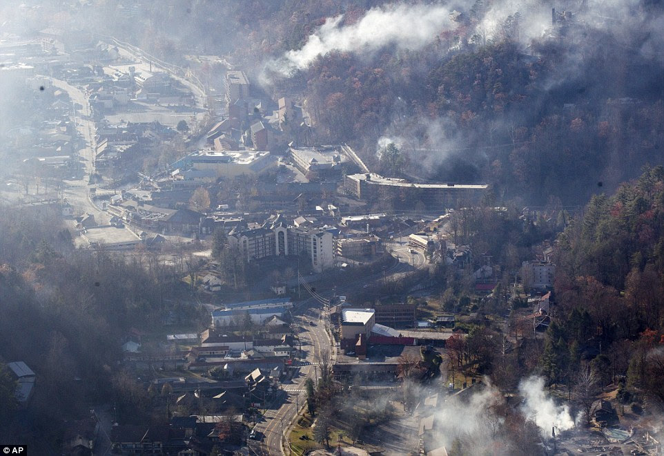 Thousands of people raced through a hell-like landscape to escape wildfires that killed several people and destroyed hundreds of homes in the Great Smoky Mountains