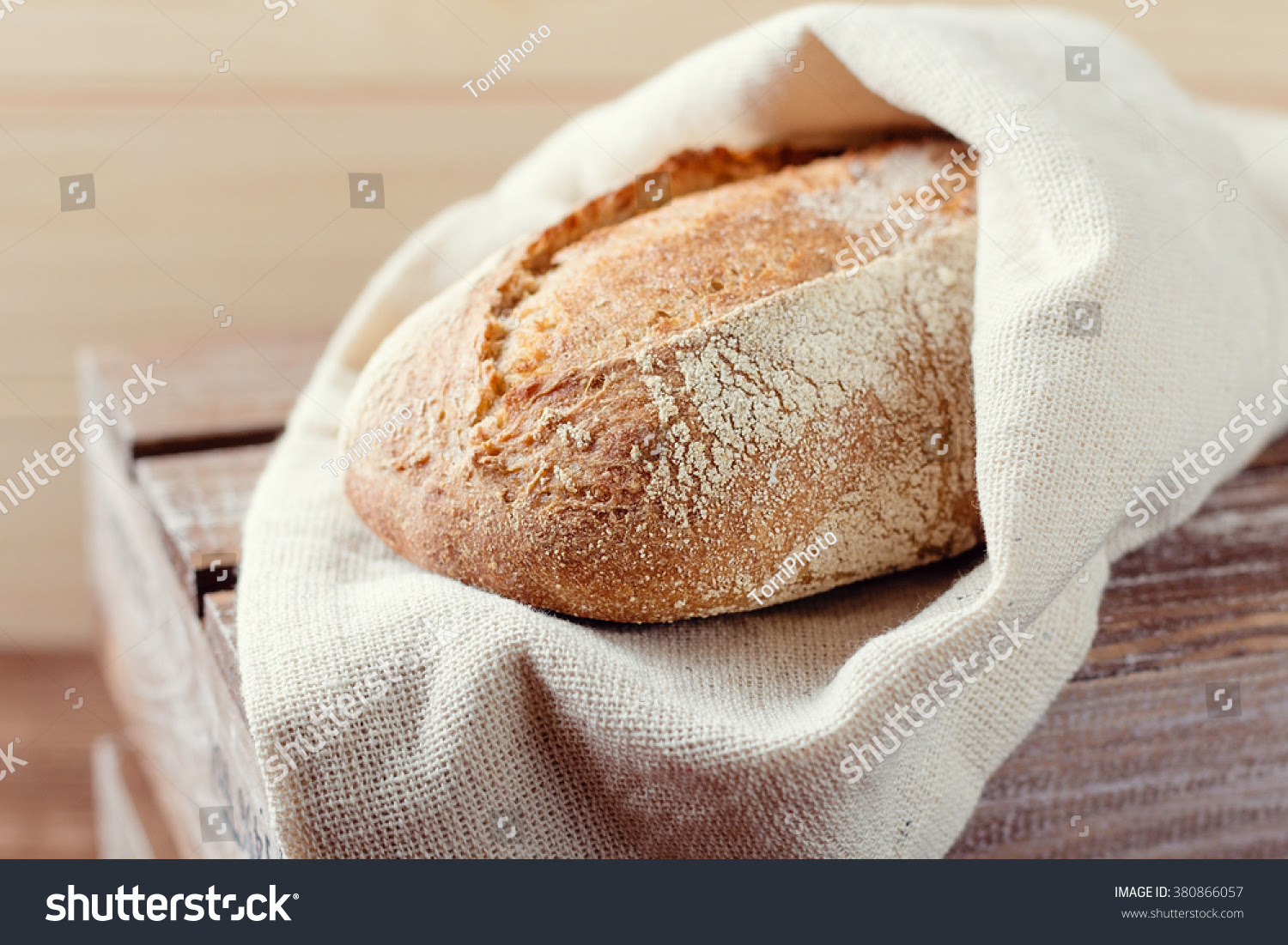 http://www.shutterstock.com/pic-380866057/stock-photo-fresh-bread-wrapped-in-a-linen-cloth-on-a-wooden-background-shallow-focus.html